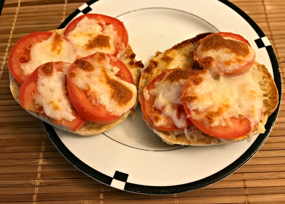 toasted bialy with melted mozzarella cheese and plum tomato